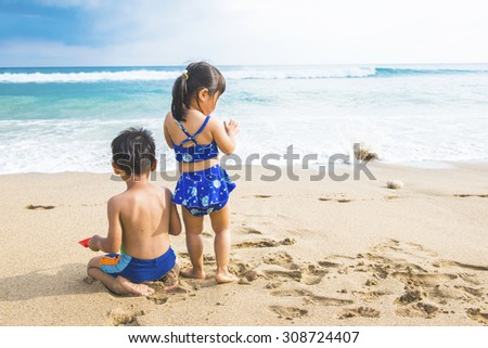 Little boy and girl sitting on the sand - stock photo