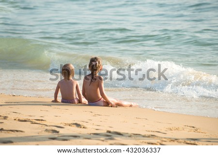 Little boy and girl sitting on the sand, sitting together in the sand looking at the sea, Blurred background - stock photo