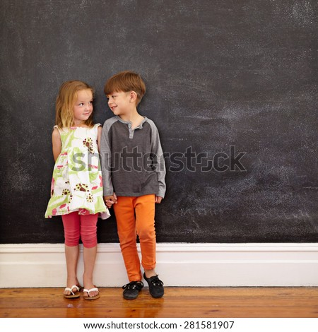 Little boy and girl standing in front of blackboard looking at each other. Indoors shot of children at home with copy space. - stock photo