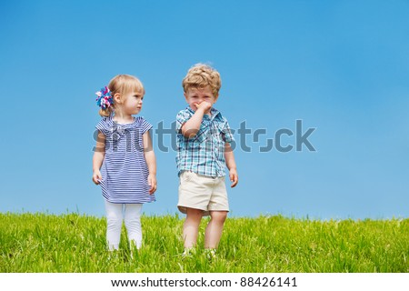 Little boy and girl standing on the hill - stock photo