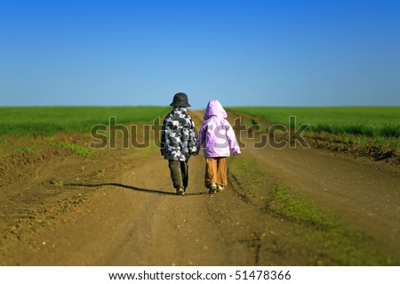 Little boy and girl walking through field a bright spring's day - stock photo