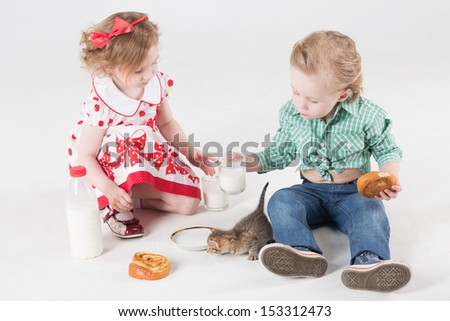 Little boy and girl with a kitten drinking milk and eating buns - stock photo