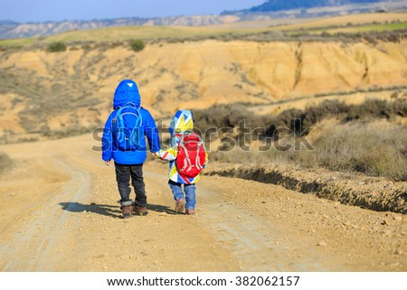 little boy and girl with backpacks travel on the road to mountains - stock photo