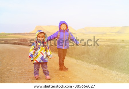 little boy and girl with backpacks travel together - stock photo