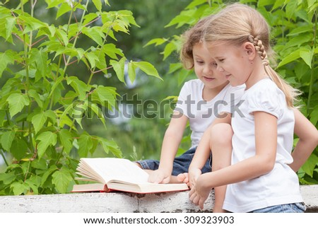 little boy and girl with book sitting in the park at the day time - stock photo