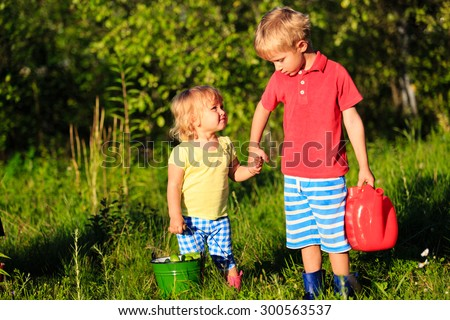 little boy and girl working in the garden, kids harvesting - stock photo