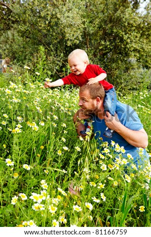 little boy and his father enjoying outdoors in field of flowers on a summer day - stock photo