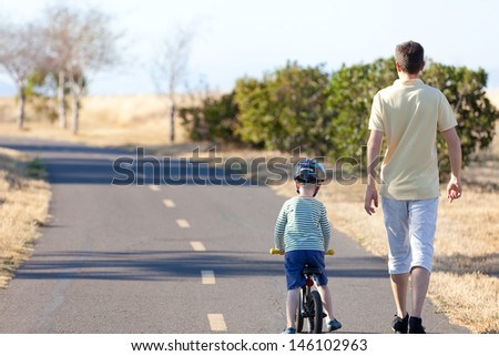 little boy and his father having a nice walk together at summer - stock photo
