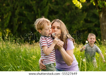 Little boy and his mother blowing dandelion seed for a whish on a meadow outdoors in summer, in the background his brother is running - stock photo
