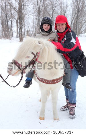 little boy and his mother with the little horse - stock photo