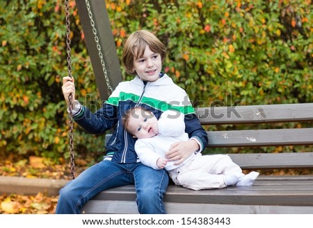 Little boy and his newborn baby sister relaxing on a wooden swing in a colorful garden with red, yellow and golden trees - stock photo