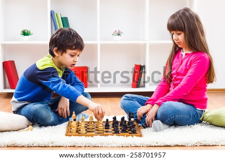 Little boy and little girl are playing chess at home.Children playing chess - stock photo