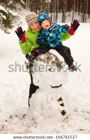 Little boy and mother posing on big snowman in winter - stock photo