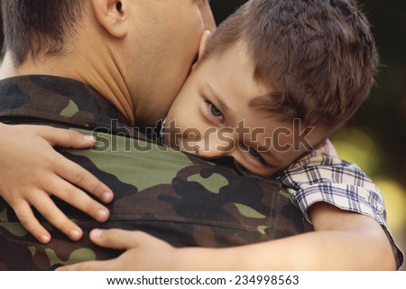 Little boy and soldier in a military uniform say goodbye before a separation - stock photo