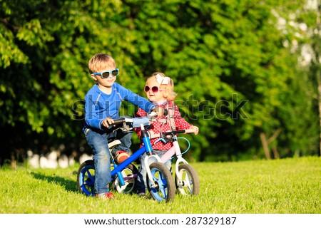 little boy and toddler girl on bikes in summer park, kids sport - stock photo