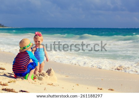 little boy and toddler girl playing with sand on tropical beach - stock photo