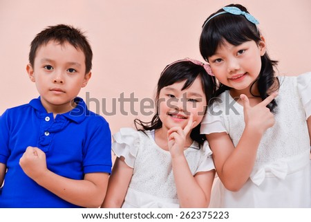little boy and two little girl standing isolated on pink background - stock photo