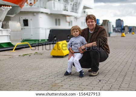 Little boy and young happy father having fun in city harbor, Germany, Kiel - stock photo