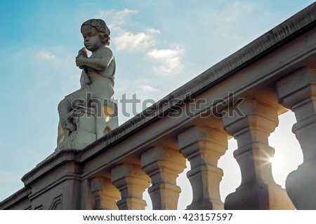 Little boy angel sculpture sits on the bridge construction and gesticulates. Blue sky background - stock photo