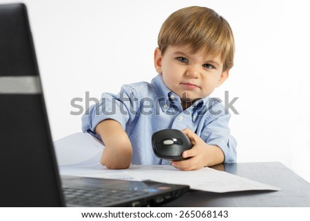 Little boy angry with laptop and papers - stock photo