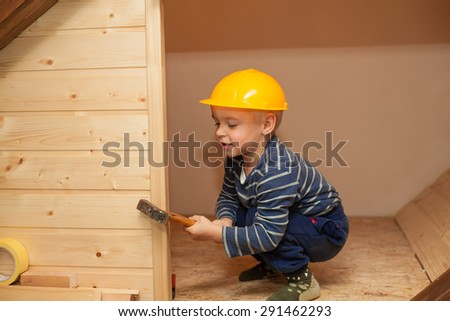 Little boy as a construction worker with hammer and hellmet. - stock photo