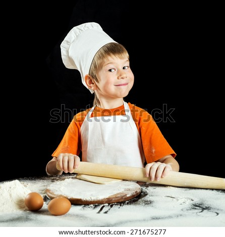 Little boy as chef  making pizza or pasta dough. Isolated on black. - stock photo