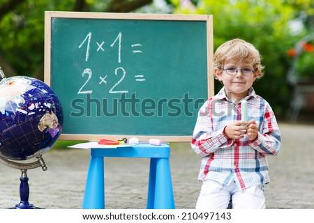 Little boy at blackboard practicing mathematics, outdoor school or nursery. Back to school concept - stock photo