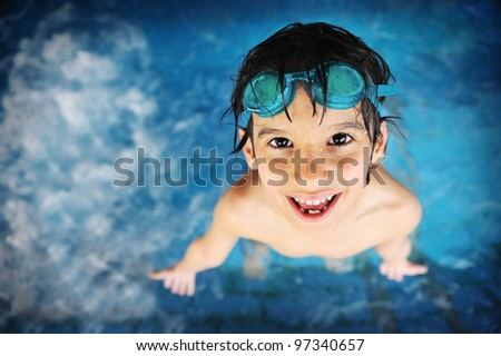 Little boy at swimming pool with goggles - stock photo