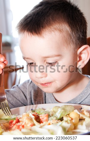 little boy at the kitchen table with food - stock photo