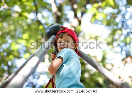 Little boy at top of jungle gym, outdoor portrait - stock photo