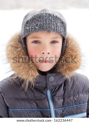 Little boy at wintertime with warm coat - stock photo