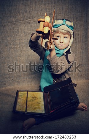 Little boy aviator dreaming and playing with wooden handmade toy plane over vintage canvas background - stock photo