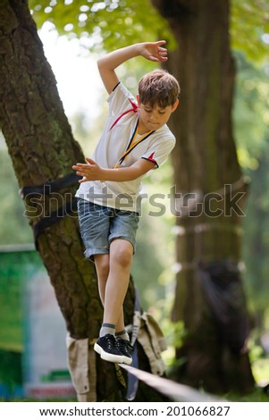 Little boy balancing on a tightrope on the background of trees in the park - stock photo