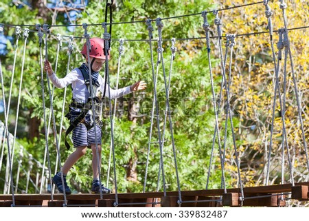 little boy being active at treetop adventure park - stock photo