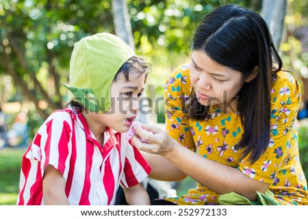 Little boy Bleeding at the mouth and mother help first aid to him - stock photo