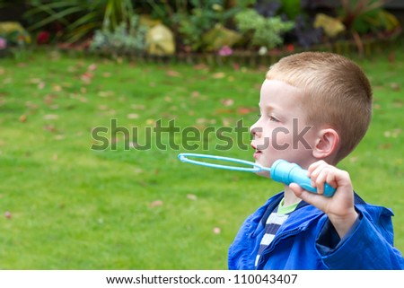 little boy blowing big colourful bubbles in the garden - stock photo