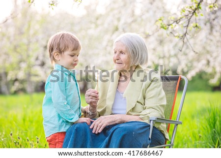 Little boy blowing dandelion seeds while his great grandmother is holding a flower - stock photo