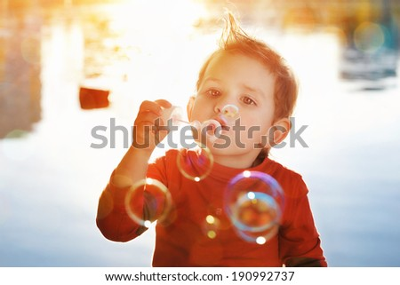 Little boy blowing soap bubbles at a lake - stock photo