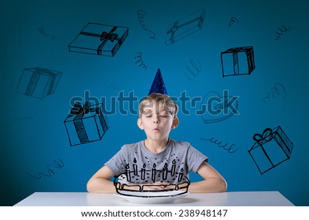 Little boy blowing the candles on his birthday cake - stock photo