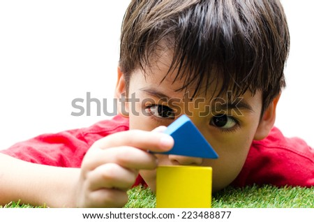 little boy building a small house with colorful wooden blocks - stock photo