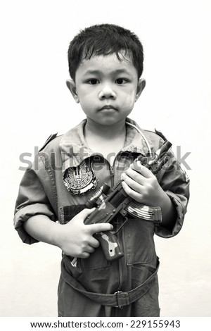 Little  boy carrying a machine gun like a soldier - stock photo