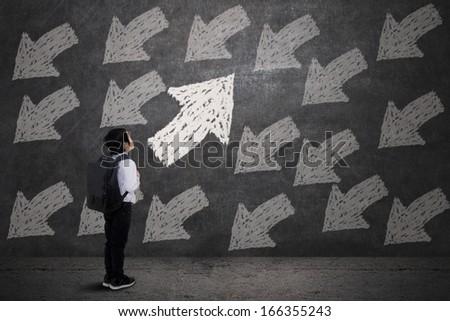 Little boy carrying backpack, looking at arrows on blackboard - stock photo