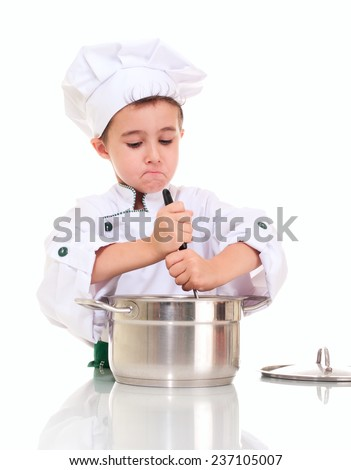 Little boy chef with ladle stirring in the pot by both hands isolated on white - stock photo