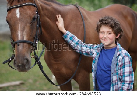 little boy clean his horse - stock photo