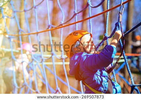 little boy climbing in adventure activity park with helmet and safety equipment - stock photo