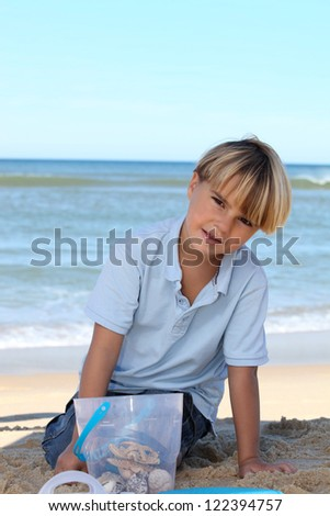 Little boy collecting starfish in a bucket on the beach - stock photo