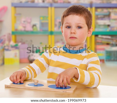 little boy collects a puzzle on a background of shelves cluttered with toys - stock photo