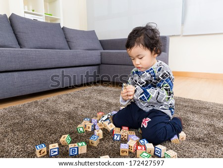 Little boy concentration on playing wooden toy block  - stock photo