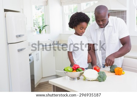 Little boy cooking with his father in the kitchen - stock photo