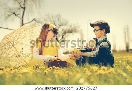 little boy courting a girl of the park in a flower meadow.vintage-look/little boy courting a girl - stock photo